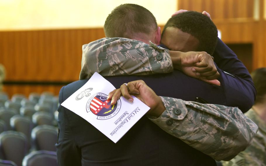 Senior Airman Walter Boze, holding program, embraces Tech. Sgt. Robert Davis after the memorial service on Tuesday, Oct. 22, 2019, for Airmen 1st Class Jacob A. Blackburn and Bradley Reese Haile at Spangdahlem Air Base, Germany. Blackburn and Haile were killed last month in car crash on base.