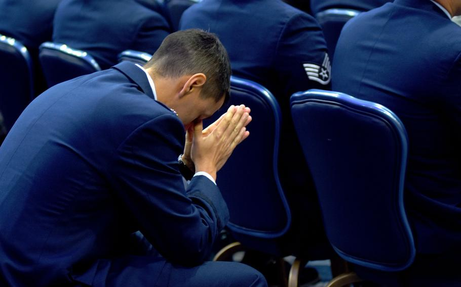 An airman prays during a memorial service for Airmen 1st Class Jacob A. Blackburn and Bradley Reese Haile on Tuesday, Oct. 22, 2019, at Spangdahlem Air Base, Germany. Blackburn and Haile were killed in a car crash on base last month.