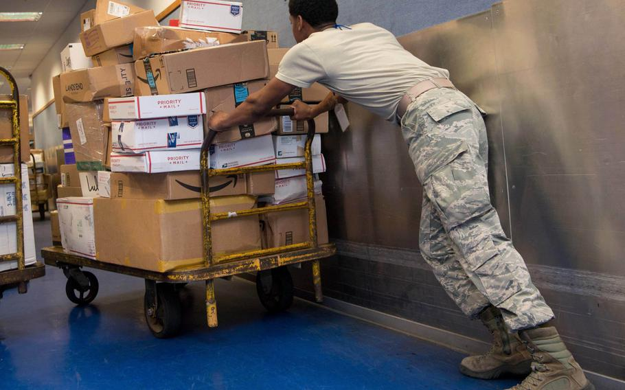 A U.S. Air Force airman pushes a cart of parcels at Ramstein Air Base, Germany's  North Side Post Office in 2017. Space-available mail coming from the U.S. to Air Force postal offices in Germany, Belgium and the Netherlands will take around 30 to 45 days to arrive during the upcoming holiday season.