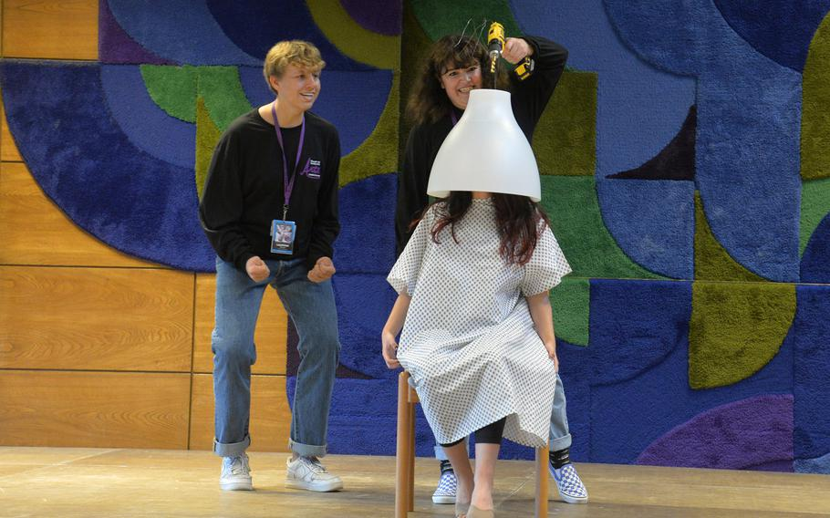 Maggie Joyce of SHAPE pretends to drill a hole in Bahrain?s Lujane Yacoub's head as Laurynas Bruzga of Ankara watches in the avant-garde collective workshop at this year?s Creative Connections in Oberwesel, Germany, Monday, Nov. 4, 2019.