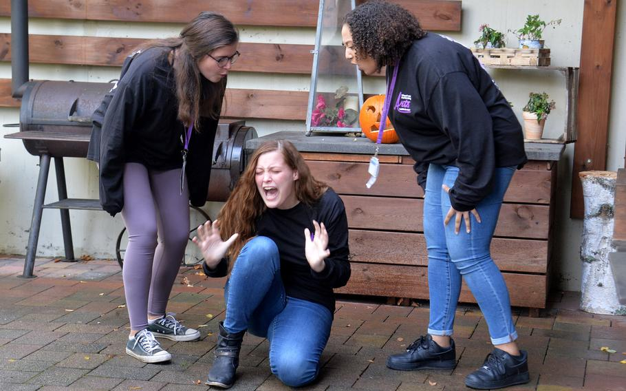 Spangdahlem's Jolie Haar screams as Rota's Helen Quast, left, and Bahrain's Jasmine Osman put her down, saying she has stage fright, as they act out a piece in the drama workshop at Creative Connections.
