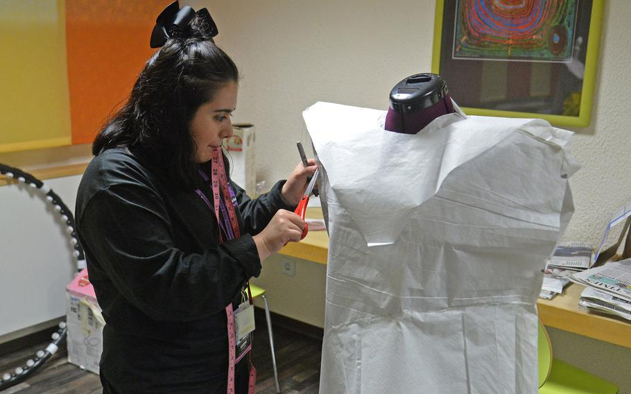 Kaiserslautern's Karen Acosta snips a costume she is making in the costume design workshop at Creative Connections in Oberwesel, Germany, Monday, Nov. 5, 2019.
