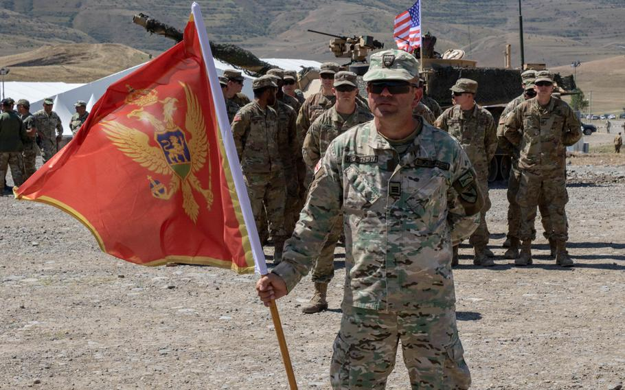 A soldier holds a Montenegrin flag during the closing ceremony of the multinational Agile Spirit 19 exercise at Orpholo Training Area, Georgia, in August 2019. NATO is deploying a team specialized in countering hybrid warfare threats to Montenegro, its newest member state, ahead of elections in the Balkan state next year.