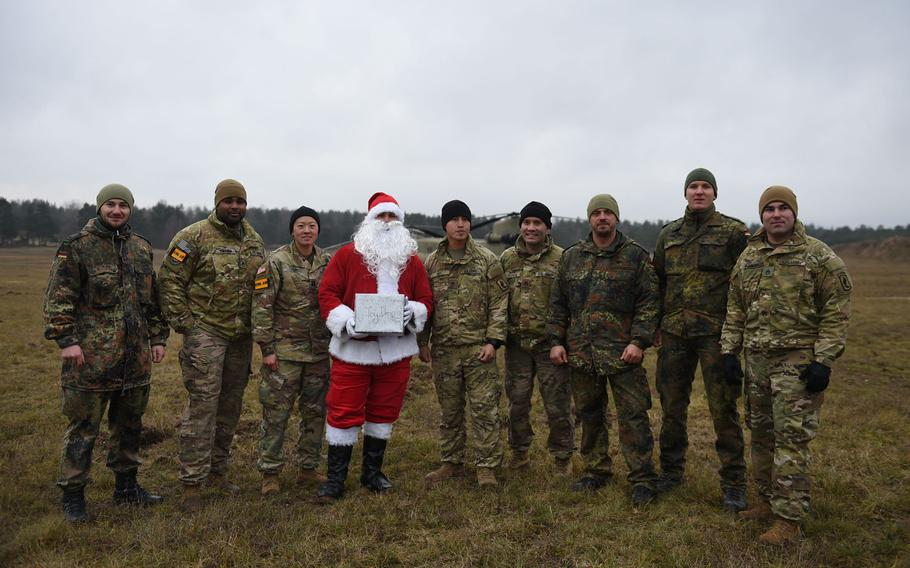 German soldiers, U.S. soldiers from the 4-319th Field Artillery Regiment and Santa Claus pose at the Grafenwoehr Training Area, Germany, on Dec. 12, 2019. Soldiers marched to deliver toys from a drop zone to Tower Barracks for children through Haus St. Elisabeth in Windischeschenbach, Germany.