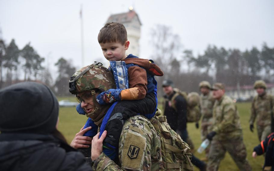 Maj. Jason Byers, left, the chaplain with the 41st Field Artillery Brigade, carries his son, Lincoln Byers, to the end of a march at Grafenwoehr, Germany, on Dec. 12, 2019. Soldiers marched to deliver toys from a drop zone to Tower Barracks to a German home for children.