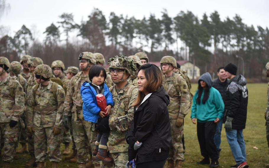 First Sgt. Brian Lomibao, center, holds his son Eliot, who's clutching the goodie bag the family got for taking part in a 3-mile march on Grafenwoehr Training Area in Germany, as part of a holiday toy collection for needy children.