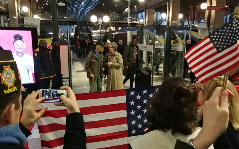 Stephen Weiss, an American World War II veteran who worked with the Office of Strategic Services behind enemy lines in France in 1944, is greeted by Meredith Wheeler, an American expatriate living in southern France, and other American well-wishers at Paris's Gare du Nord train station on Thursday, Feb. 13, 2020.