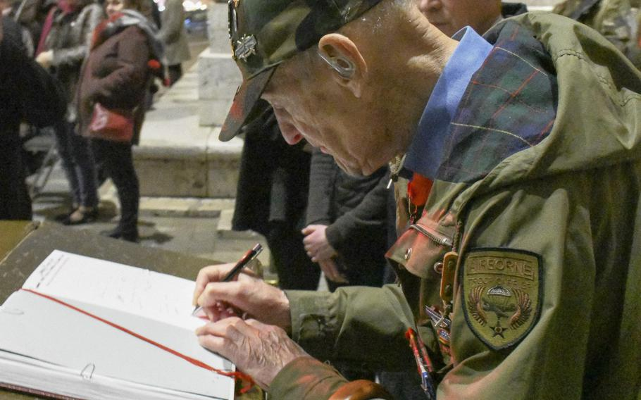 Stephen Weiss, an American World War II veteran living in London, signs a commemorative book following a ceremony to rekindle the Eternal Flame at the Tomb of the Unknown Soldier under the Arc de Triomphe in Paris on Friday, Feb. 14, 2020. The ceremony honored the Office of Strategic Services, which Weiss, 94, had worked with behind enemy lines after being separated from his infantry unit during WWII.
