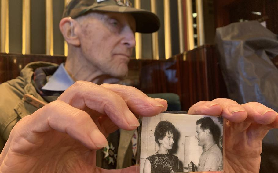 In a Parisian cafe on Friday, Feb. 14, 2020, Stephen Weiss, 94, shows off a photo of himself with Italian actress Sophia Loren during his early post-World War II career in Hollywood. Weiss, a war and trauma researcher based in London, battled post-traumatic stress disorder after the war, but credits therapy with helping him turn his life around and lead three successful careers in his long life.