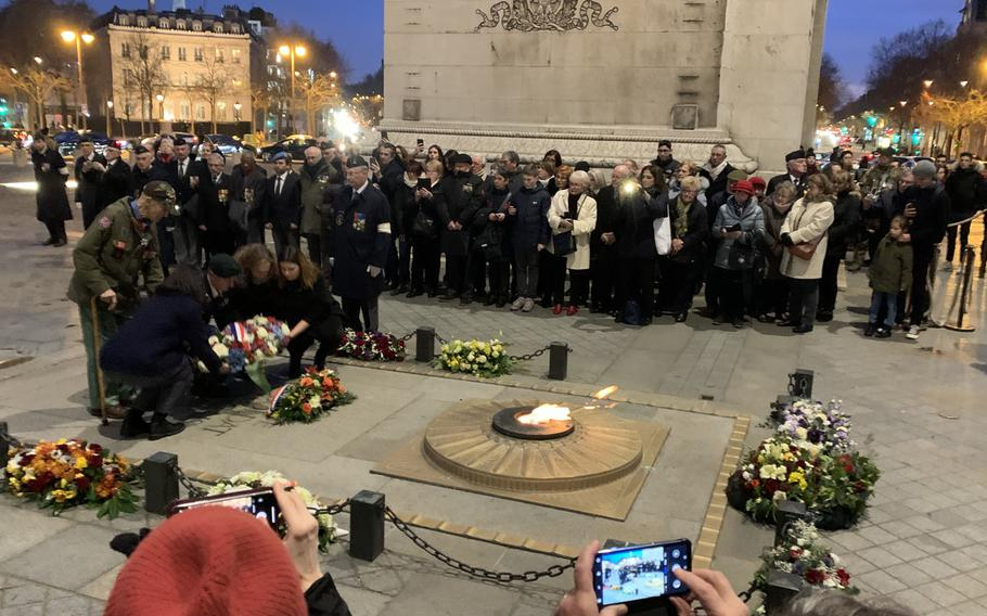 Stephen Weiss, 94, standing on the left, helped lay a wreath at the Eternal Flame at the tomb of France's unknown soldier under the Arc de Triomphe on Friday, Feb. 14, 2020, along with, left to right, French-American high school student Margot Sarkozy, Special Forces Lt. Col. Travis Moliere, Beatrice Boussens, the grandaughter of an Italian-Jewish member of the Office of Strategic Services, and French-American high school student Josephine Ligout. Weiss is one of the few American World War II veterans alive who worked with the OSS behind enemy lines in France during the war. Sarkozy and Ligout had won national prizes from a French veterans organization.