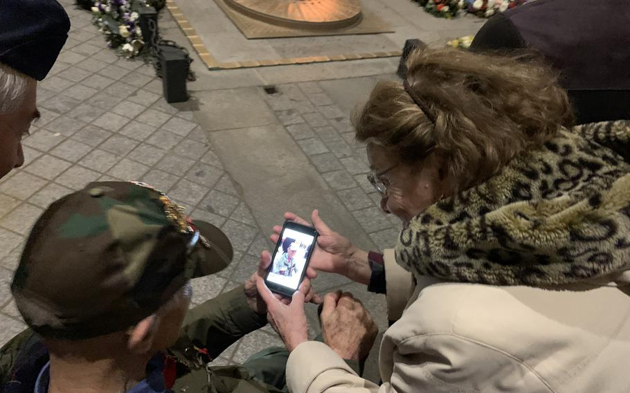A French woman shows American World War II veteran Stephen Weiss a photo she took of him at France's Tomb of the Unknown Soldier during a twilight ceremony under the Arc de Triomphe on Friday, Feb. 14, 2020.