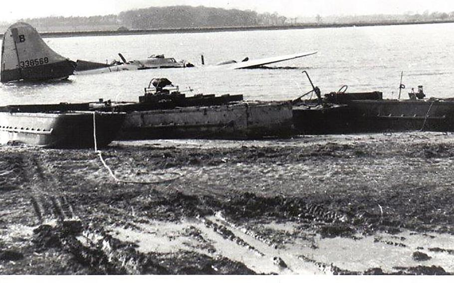 The B-17 Flying Fortress that crashed on Feb. 20, 19945 in the Deben River near the east coast of England is shown just prior to being hauled ashore by recovery barges.  Eight of the bomber's crew of 10 died in the crash, which happened shortly after the plane took off on a mission to Nuremberg, Germany.