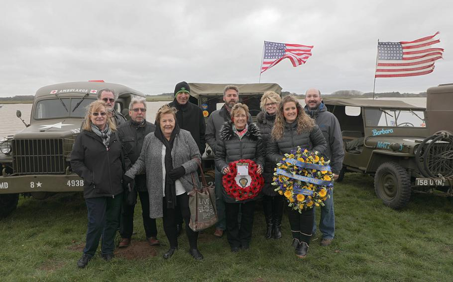 Family members of the crew of a B-17 bomber that crashed in a river in England during World War II pose for a group photo prior to a remembrance ceremony for their crew held in Ramsholt, England Feb. 20, 2020.