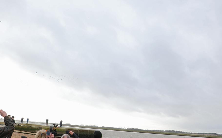 A U.S. Air Force C-130 and CV-22 from RAF Mildenhall are watched as they fly over the Deben River in England on Thursday, Feb. 20, 2020, 75 years to the day that an American B-17 Flying Fortress crashed there, killing eight of the 10 crew on board.