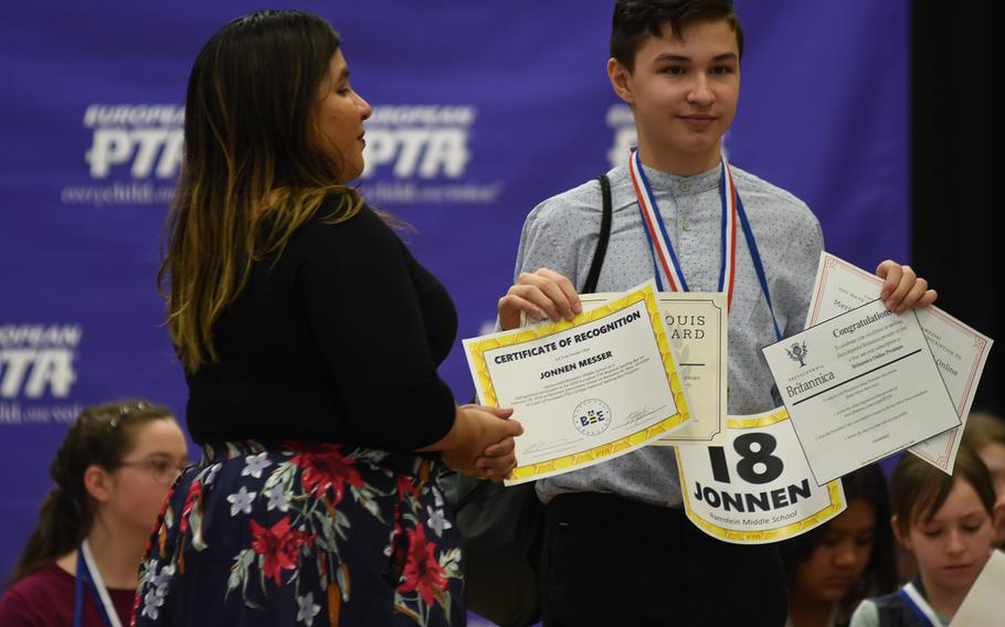 Spelling bee champion Jonnen Messer, a seventh grader at Ramstein Middle School, Germany, holds up his prize certificates at the the conclusion of the European PTA Regional Spelling Bee on Saturday, Feb. 29, 2020, at Ramstein Air Base.