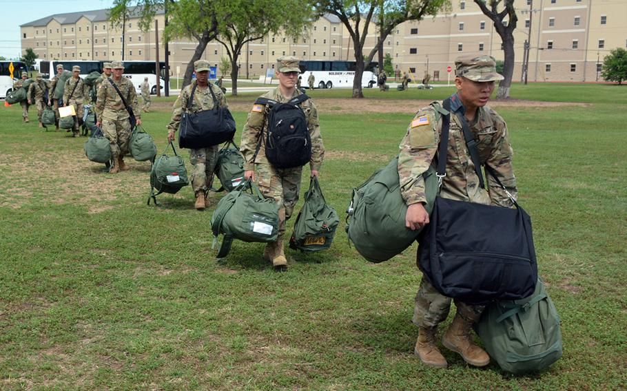 U.S. Army combat medics arriving at Fort Sam Houston, Texas, for training, move in formation while maintaining proper social distancing after departing from their travel bus.