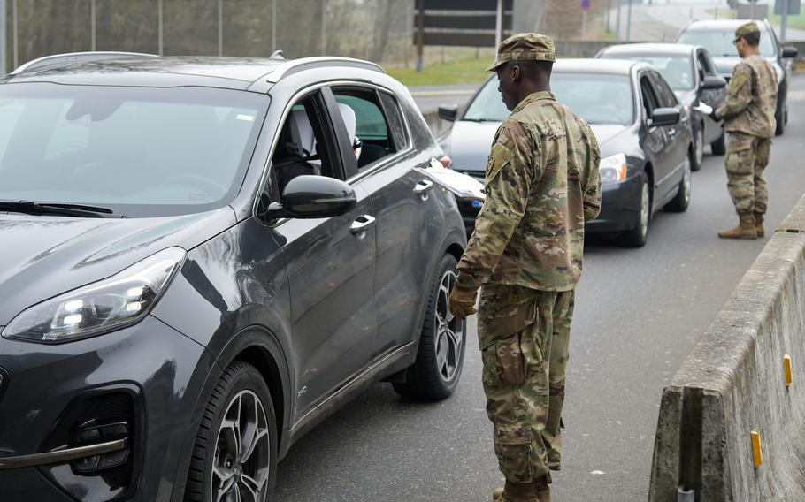 U.S. soldiers assigned to 2nd Squadron, 2nd Cavalry Regiment ask health questions to people entering Rose Barracks, Vilseck, Germany on March 18, 2020, as part of the military's coronavirus response.