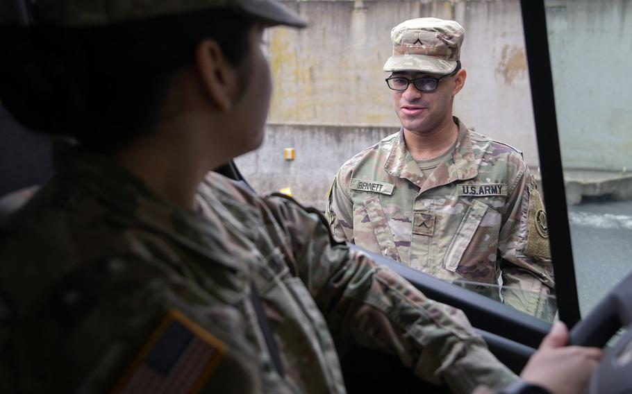 U.S. Army Pvt. Rapheal Bennett, 2nd Squadron, 2nd Cavalry Regiment, asks health questions to a service member entering Rose Barracks, Vilseck, Germany on March 18, 2020, as part of the military's coronavirus response.