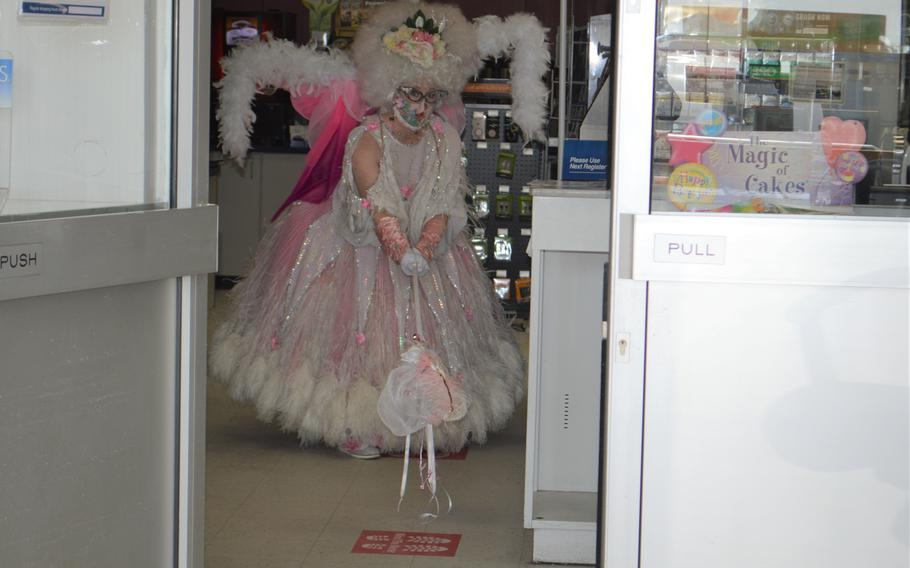 """Desse, a physical distancing fairy, points at a """"mind the meter"""" sign at the Exchange Express on Katterbach Kaserne, Germany, April 16, 2020."""