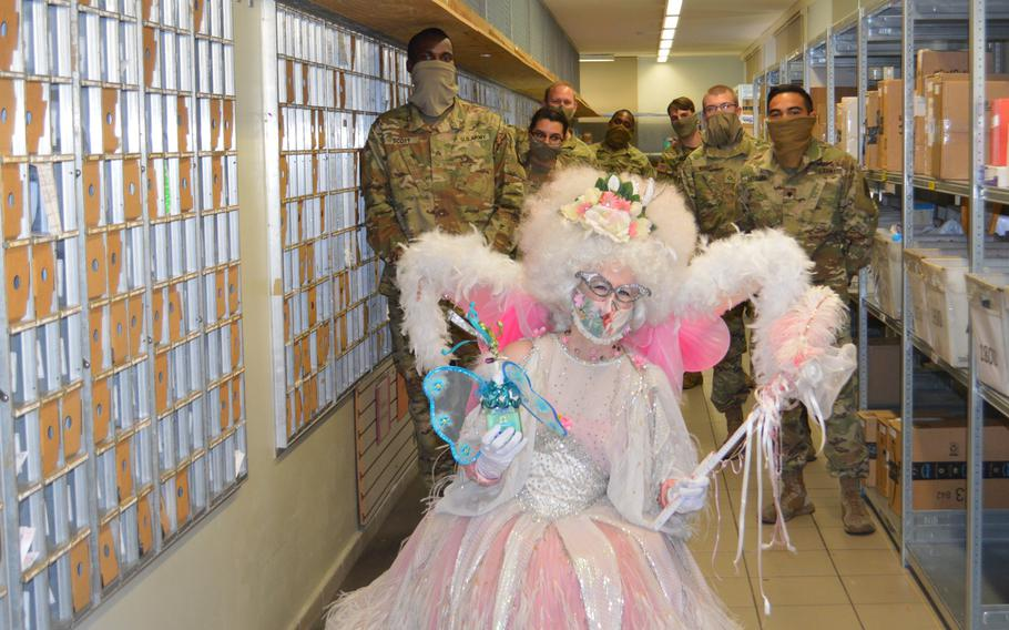 Desse, a physical distancing fairy, poses with 164th Air Defense Artillery Brigade and 12th Combat Aviation Brigade soldiers, who are volunteering at the post office, on Katterbach Kaserne, Germany, April 16, 2020.