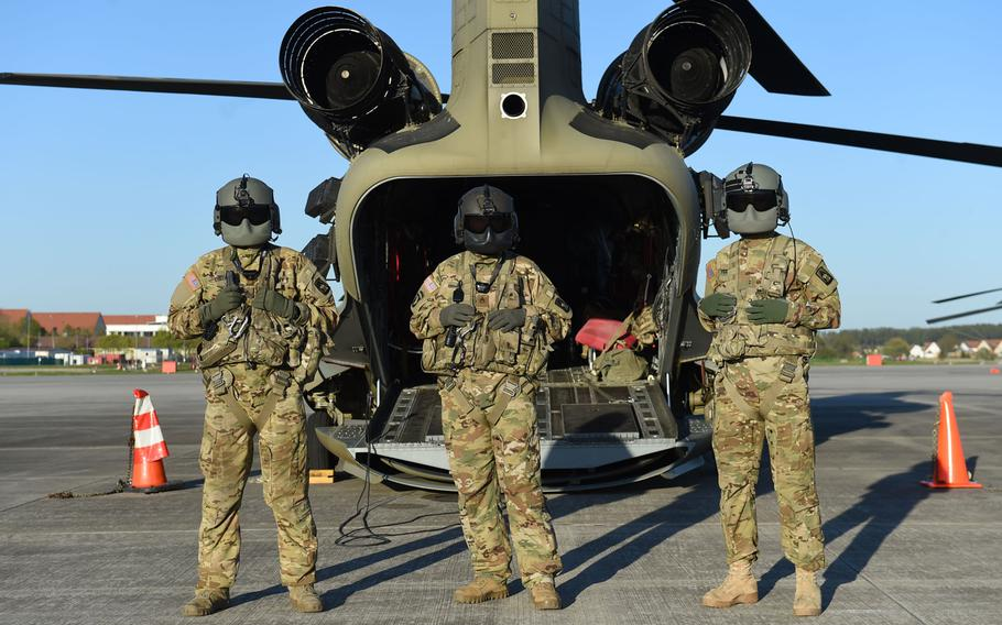 From left, Sgt. Matthew Cullen, a flight engineer, Staff Sgt. Elijah Joice, a flight engineer instructor, and Chief Warrant Officer 2 Dylan Hawkins, an aviator, all with the 12th Combat Aviation Brigade, stand in front of a CH-47 Chinook helicopter before a pilot progression training exercise on Ansbach, Germany, April 20, 2020. The training went ahead, with modifications, in spite of the coronavirus pandemic.
