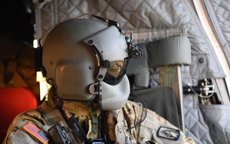 Sgt. Matthew Cullen, a flight engineer with the 12th Combat Aviation Brigade, looks out of a CH-47 Chinook helicopter during a pilot progression training exercise on Ansbach, Germany, April 20, 2020.