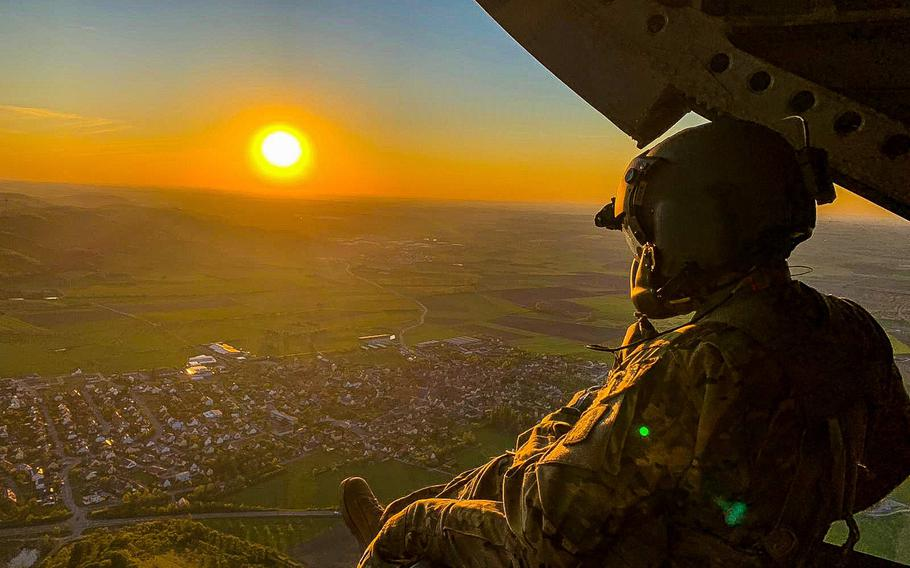 Sgt. 1st Class Manuel Reyes, a crew chief with the 12th Combat Aviation Brigade, looks out of a CH-47 Chinook helicopter during a pilot progression training exercise on Ansbach, Germany, April 20, 2020. The training went ahead, with modifications, in spite of the coronavirus pandemic.