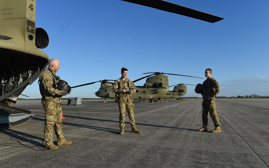 From left, Staff Sgt. Elijah Joice, a flight engineer instructor, 1st Lt. Timothy Mills, a pilot, and Chief Warrant Officer 2 Dylan Hawkins, a pilot, all with the 12th Combat Aviation Brigade, conduct a safety brief before a pilot progression training exercise on Ansbach, Germany, April 20, 2020.