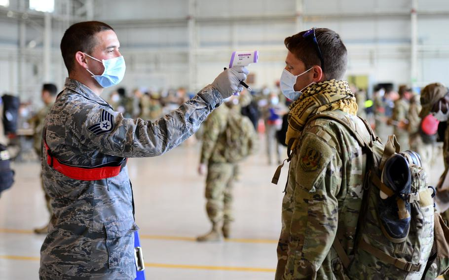 An 31st Medical Group airman takes the temperature of an airman returning from deployment, as part of a coronavirus screening, at Aviano Air Base, Italy, April 18, 2020.
