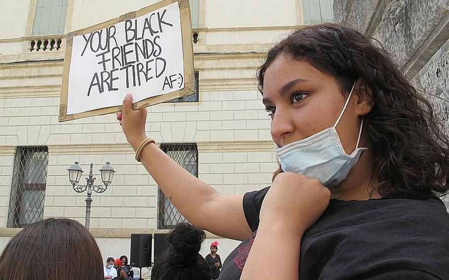 """An Italian woman at a protest in Vicenza, Italy on Saturday, June 6, 2020, held a sign expressing the fatigue black people are experiencing after centuries of exploitation, discrimination and state-sponsored violence. The other side said,""""I Love Being Black. S--t Dangerous But It's Lit."""""""