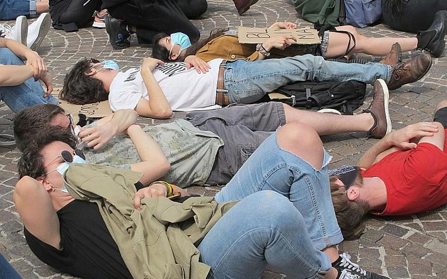 Demonstrators against U.S. racism and police brutality gathered in Vicenza, Italy on Saturday, June 6, 2020, lay on the ground after hearing a tape of the police killing of George Floyd, in which Floyd repeatedly said he couldn't breathe. Floyd died after a white police officer kept his knee pressed to Floyd's neck for nearly nine minutes.