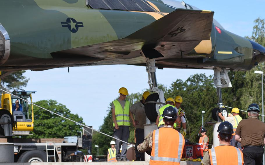 Personnel at Ramstein Air Base, Germany, help secure the wheels of a refurbished F-4 Phantom fighter jet on concrete pedestals by the northside gym, where the aircraft is on static display, June 8, 2020.