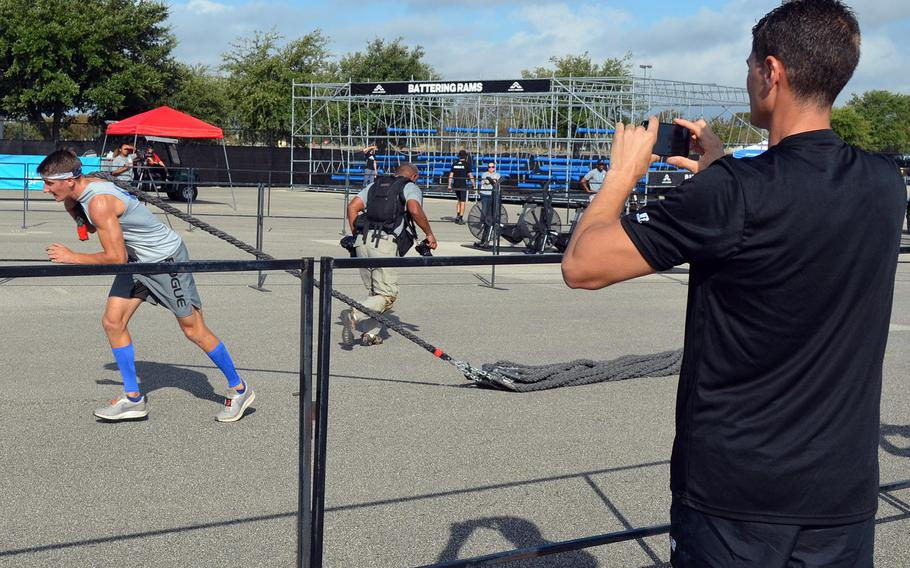 """Army Lt. Col. Eric Palicia of U.S. Army Europe watches his younger brother, Air Force Capt. Noah Palicia of Yokota Air Base, Japan, compete at the Alpha Warrior Proving Ground in San Antonio in September 2019. The two brothers are now competing on """"The Titan Games,"""" which is airing on NBC."""