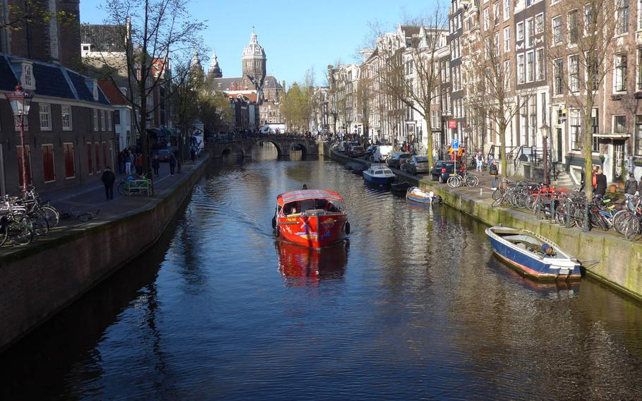 A boat plies an Amsterdam canal in April 2015.  Personnel assigned to U.S. Army Garrison Rheinland Pfalz may travel internationally but only to about 25 countries in Europe, a new general order from 21st TSC says.
