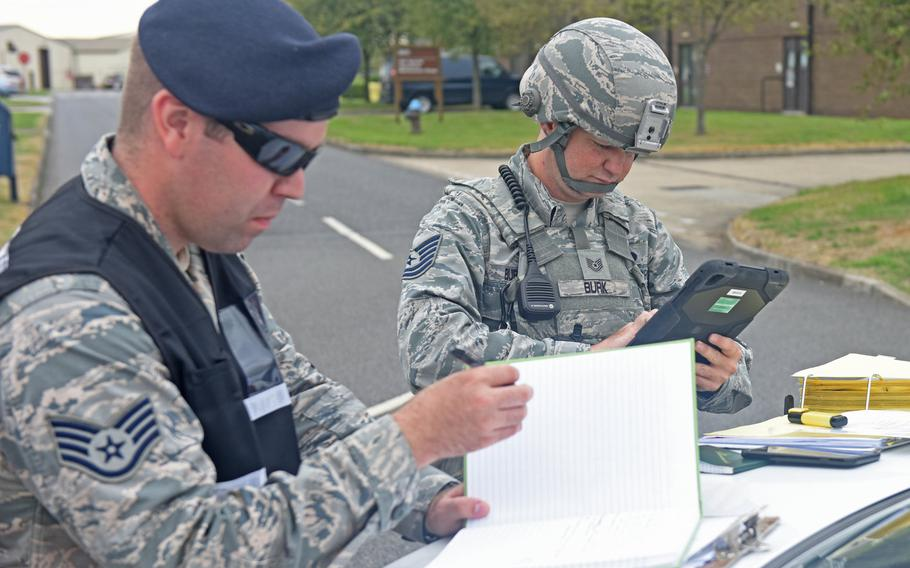 Air Force Staff Sgt. Jeremiah Johnson, left, of the 100th Security Forces Squadron, references his checklist as the on-scene commander during a mission assurance exercise at RAF Mildenhall, England, in August 2018. Johnson died at his off-base home June 27, 2020.
