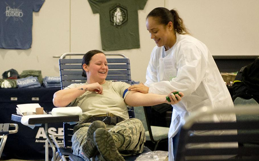 Lena Sapp, a medical technologist from Landstuhl Regional Medical Center, right, applies a tourniquet to Senior Airman Jordan Burge during a blood drive at Ramstein Air Base, Germany in February 2018. The Food and Drug Administration has loosened restrictions on who can give blood, making potentially thousands more troops, veterans and retirees who have lived in Europe eligible to donate.