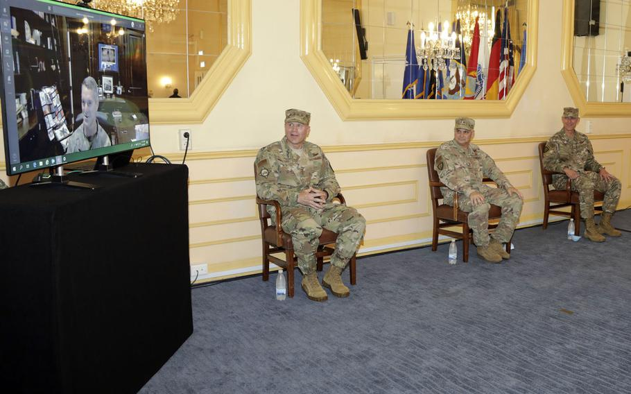 Gen. Tod D. Wolters, head of U.S. European Command,  Special Operations Command Europe outgoing commander Maj. Gen. Kirk W. Smith and incoming commander Maj. Gen. David H. Tabor listen to Gen. Richard D. Clarke, commander of U.S. Special Operations Command who is taking part virtually at the change of command ceremony in Stuttgart, Germany, Aug. 3, 2020.