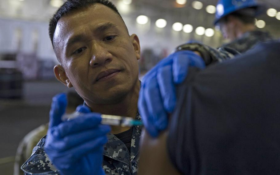 Hospital Corpsman 1st Class Ronald Valdez administers a flu shot to a sailor aboard the USS Gerald R. Ford, Oct. 16, 2018. While some military commands in Europe have begun mass vaccination campaigns for flu, U.S. Navy health officials in Naples, Italy, say they may not have the vaccine until December.