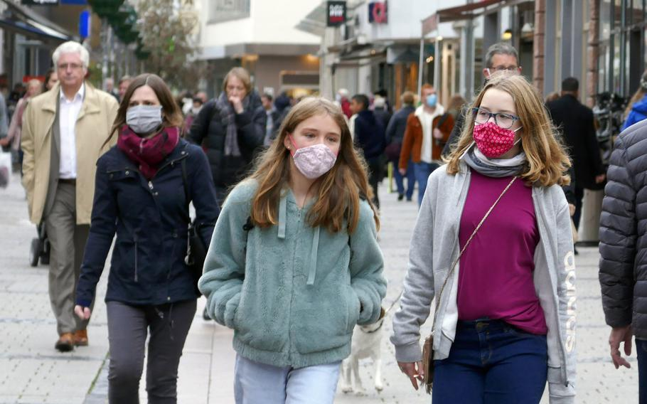 Some people wear face masks as they walk through the pedestrian zone in downtown Kaiserslautern, Germany, in mid-October 2020.