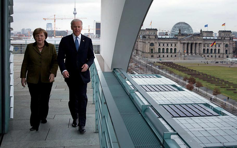 Then-Vice President Joe Biden and German Chancellor Angela Merkel walk on the balcony outside the chancellor's office overlooking Berlin, Germany, in February 2013.  President-elect Joe Biden is expected, in one of his first military policy moves, to reverse the Trump administration's plan to withdraw troops from Germany.