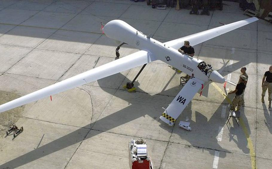 Members of the 11th Reconnaissance Squadron from Indian Springs, Nev., perform preflight checks on a Predator drone before a mission in November 2001.