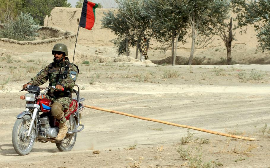An Afghan soldier drags a rake behind a motorcycle to search for roadside bombs in Zabul province.