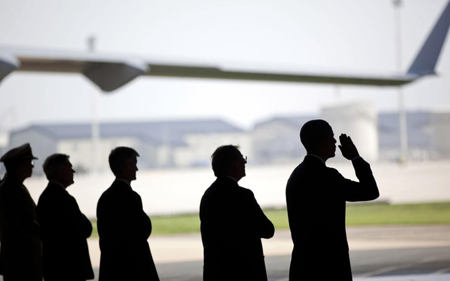 President Barack Obama, in the process of saluting, participates in a ceremony at Dover Air Force Base in Dover, Delaware on Tuesday, August 9, 2011, for the dignified transfer of U.S. and Afghan personnel who died in Afghanistan on August 6.