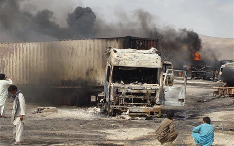 Burning NATO supply trucks are seen in Samangan, north of Kabul, Afghanistan on July 18, 2012. Afghan officials say a magnetic bomb placed on a truck exploded and destroyed 22 NATO supply vehicles in northern Afghanistan.