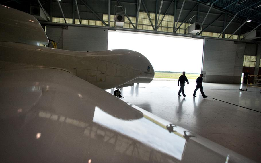Two aviation instructors walk past a model of a Northrop Grumman Global Hawk at Northland Community and Technical College in Thief River Falls, July 12, 2012.