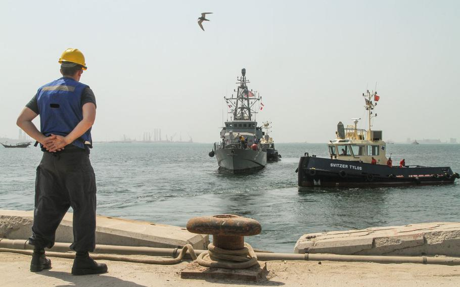 A linehandlerwaits on the pier as tug boats position the USS Tempest to gopier-sidein Bahrain for the first time.