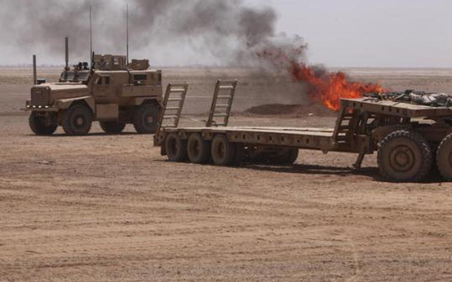 Smoke from an active burn pit at Camp Leatherneck, Afghanistan, drifts towards an MRAP vehicle June 25, 2011.