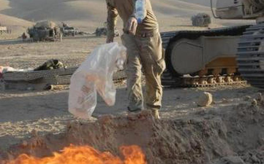 A soldier with the 24th Infantry Regiment tosses trash into a burn pit outside a checkpoint in the Zabul province of Afghanistan, Sept. 14, 2011.