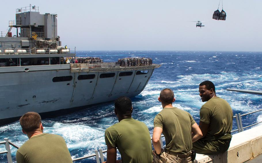 U.S. Marines assigned to the 26th Marine Expeditionary Unit sit on the flight deck before a Navy MH-60S Seahawk helicopter transports food and supplies to the USS San Antonio (LPD 17), during a resupply at sea, July 9, 2013. The 26th MEU is a Marine Air-Ground Task Force forward deployed to the U.S. 5th Fleet area of responsibility aboard the Kearsarge Amphibious Ready Group.