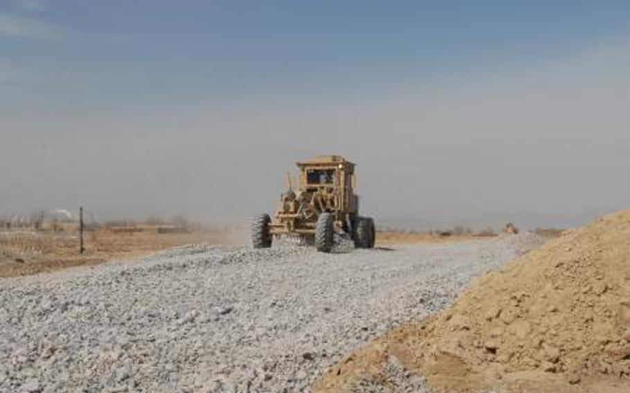 In Afghanistan, a road grader spreads gravel in Regional Command-South in February 2012. Poor contract oversight has not only wasted money; in one case, it may have led to the deaths of U.S. troops.
